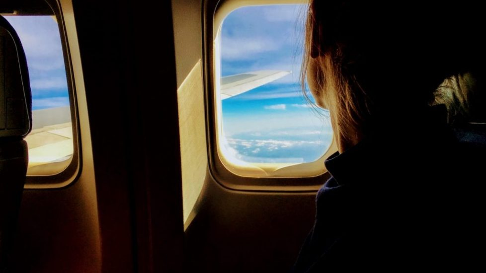 girl on a plane looking outside the window